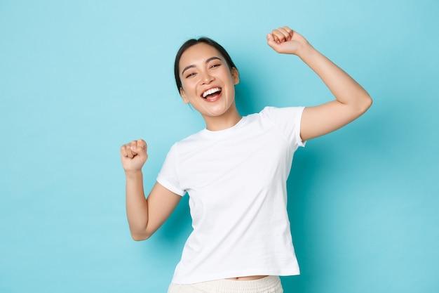 Retrato de uma garota asiática feliz e vencedora de sucesso, parecendo otimista e comemorando, erguendo os punhos e dançando como campeã, gritando sim, encantada, em pé na parede azul