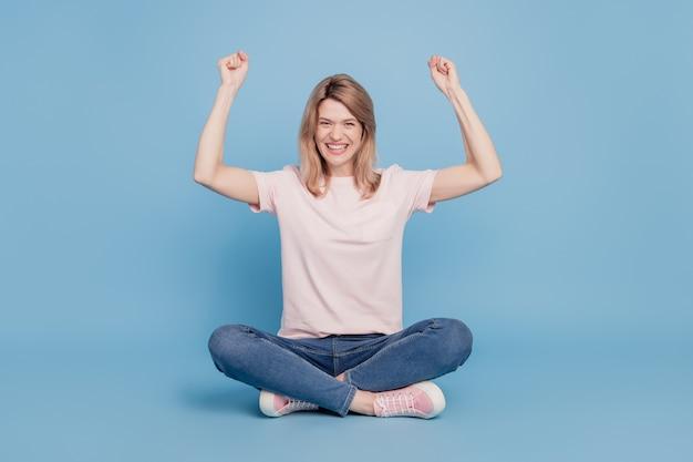 Retrato de uma garota atônita e animada sentada no chão erguendo os punhos celebrando a vitória sobre fundo azul