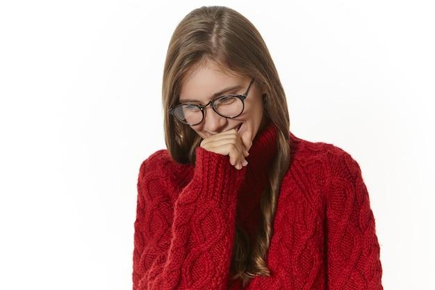 Retrato de uma garota atraente alegre com cabelo solto, segurando a mão em sua boca, rindo de uma piada ou história engraçada. jovem tímida fofa de óculos e macacão, sorrindo timidamente e olhando para baixo