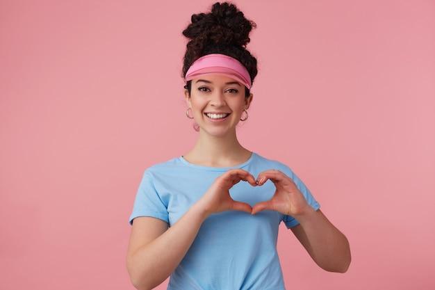Retrato de uma garota atraente, bonita, com coque de cabelo encaracolado escuro. usando viseira rosa, brincos e camiseta azul. tem maquiagem. mostrando sinal de coração