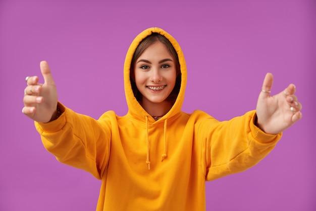 Retrato de uma garota atraente, bonita e feliz com um grande sorriso, mostra que ela quer um abraço. vestindo moletom laranja, aparelho dentário e anéis