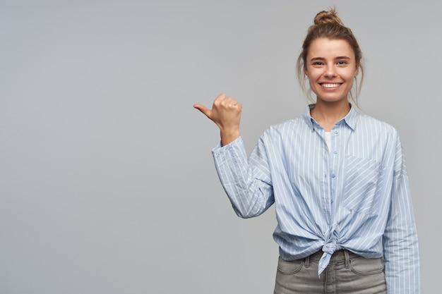 Retrato de uma garota atraente com cabelo loiro, reunido em um coque. vestindo camisa listrada com nó. apontando com o polegar para a esquerda no espaço da cópia e olhando para a câmera, isolado sobre a parede cinza