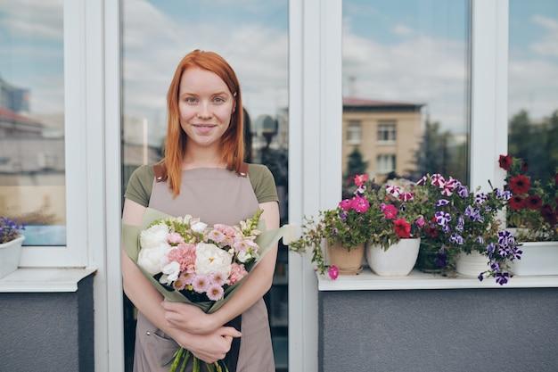 Retrato de uma garota atraente com cabelo vermelho em pé na varanda com flores em vasos no parapeito da janela e abraçando lindo buquê