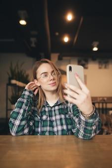 Retrato de uma garota atraente com um laptop no café, ouve música nos fones de ouvido e olha para a tela.