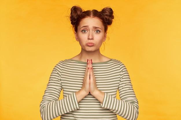 Retrato de uma garota atraente de cabelo vermelho com dois pães. vestindo um suéter listrado e parecendo triste. peça ajuda, implora perdão. fique isolado sobre a parede amarela