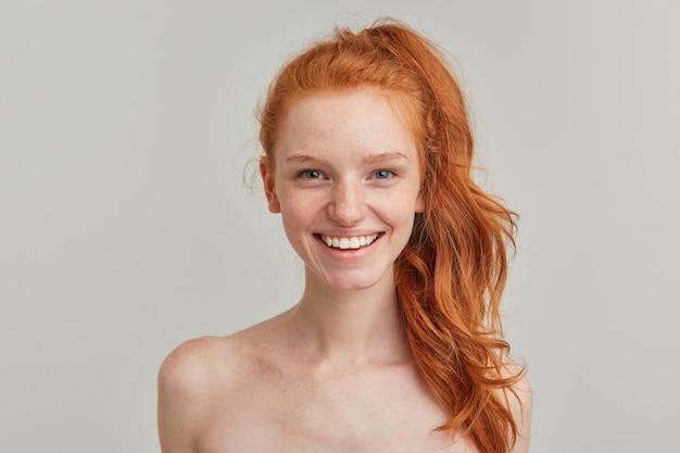 Retrato de uma garota atraente e alegre com rabo de cavalo ruivo e sardas