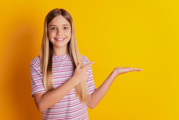 Retrato de uma garota atraente e alegre segurando anúncio de espaço vazio de dedo de palma em fundo amarelo