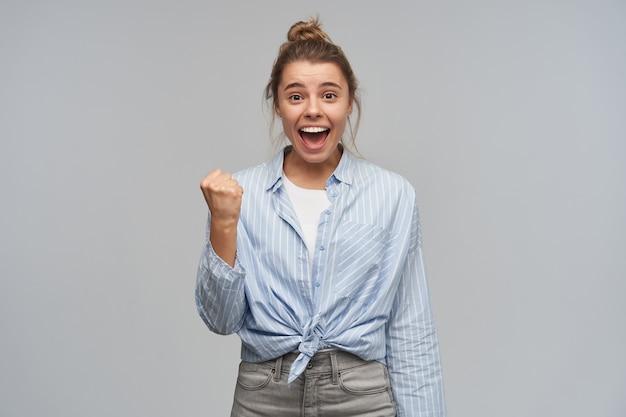 Retrato de uma garota atraente e animada com cabelo loiro reunido em um coque. vestindo camisa listrada com nó. cerrar o punho e comemorar o sucesso. olhando para a câmera, isolada sobre uma parede cinza
