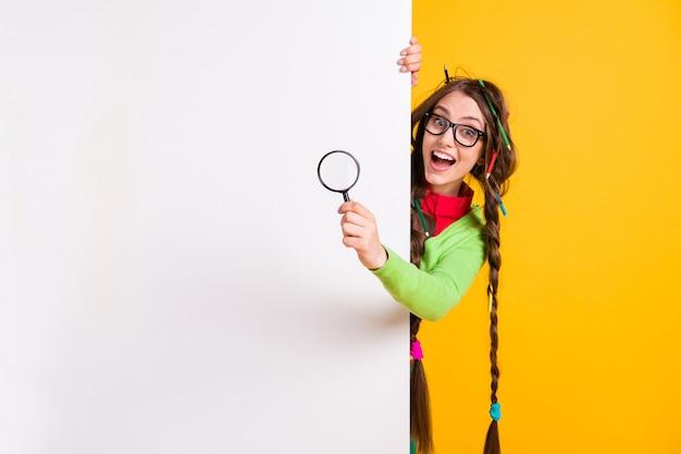 Retrato de uma garota atraente e divertida mostrando um look de pesquisa no espaço de cópia isolado sobre um fundo de cor amarela brilhante