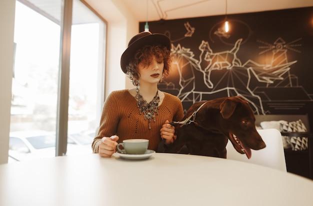 Retrato de uma garota atraente e elegante sentada com um cachorro no café à mesa e bebendo café