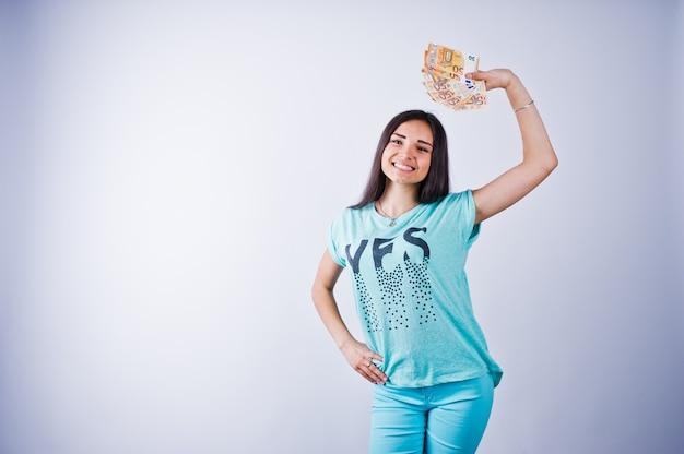 Retrato de uma garota atraente em camiseta azul ou turquesa e calça posando com muito dinheiro na mão.