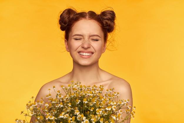 Retrato de uma garota atraente, fofa, charmosa, ruiva com pães. segurando um buquê de flores silvestres e apertando os olhos em um sorriso. pele saudável. closeup, suporte isolado sobre a parede amarela