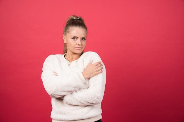 Retrato de uma garota atraente se abraçando isolada sobre uma parede vermelha
