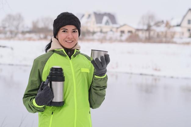 Retrato de uma garota atraente sorridente com uma faixa de malha, desfrutando de um chá quente após o treino no inverno