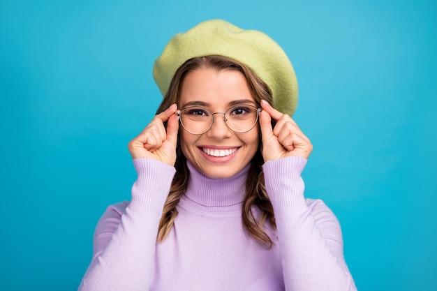 Retrato de uma garota atraente tocando suas especificações modernas na parede azul