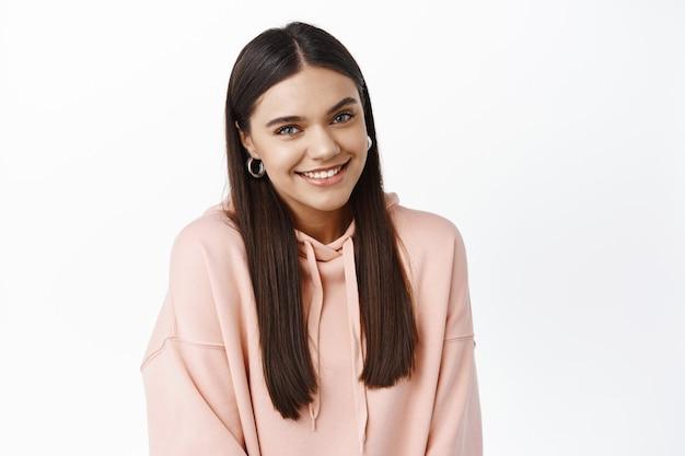 Retrato de uma garota bonita e sedutora com cabelos longos e lisos, rindo e sorrindo com dentes brancos, olhando para a frente coquete, em pé contra uma parede branca