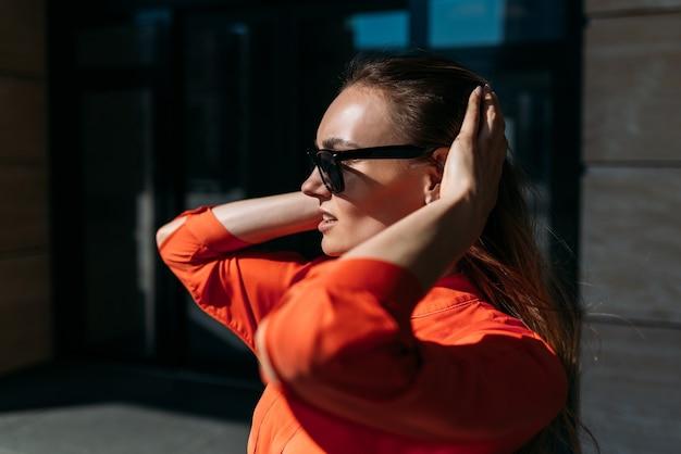 Retrato de uma garota caucasiana na moda em óculos de sol e roupas casuais