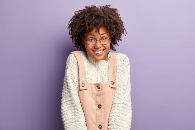 Retrato de uma garota charmosa com cabelos afro, expressão facial satisfeita, sorri amplamente, mostra dentes brancos