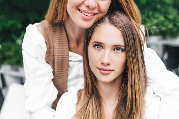Retrato de uma garota charmosa olhando para a câmera, atrás dos abraços da mãe