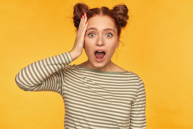 Retrato de uma garota de cabelo vermelho atraente e animado com dois pães. vestindo suéter listrado e ouvindo notícias chocantes, tocando sua cabeça. assistindo isolado sobre a parede amarela