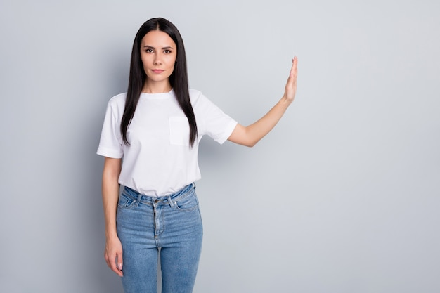 Retrato de uma garota de cabelos lisos atraente adorável, muito restrito, mostrando o sinal de parada ao lado das medidas preventivas. ncov