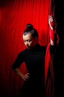 Retrato de uma garota de esportes em um fundo de panos vermelhos para ginástica aérea. filmagem de estúdio em um fundo escuro,
