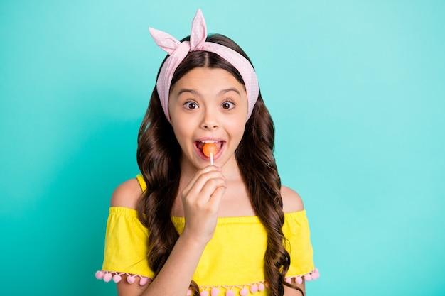 Retrato de uma garota descolada lambendo saborosos doces de chupa chups