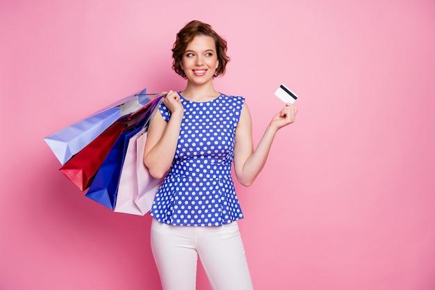 Retrato de uma garota elegante e alegre segurando um cartão de banco carregando uma sacola parece lateral