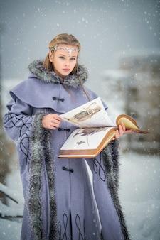 Retrato de uma garota elfa de conto de fadas com um livro de magia nas mãos, tendo como pano de fundo a natureza de inverno e a fortaleza mágica