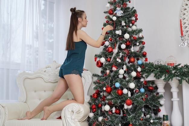 Retrato de uma garota em um penhoar verde em uma vista lateral do perfil decora uma árvore de natal, uma garota subiu em uma poltrona branca, dentro de casa