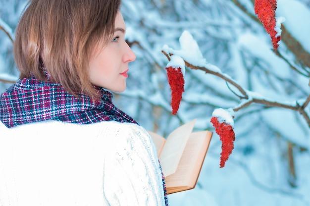 Retrato de uma garota encantadora que lê um livro na floresta de inverno. conceito de natal, celebrações de inverno, passeios na floresta, férias. mídia mista
