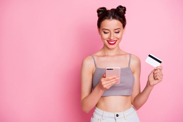 Retrato de uma garota encantadora segurando cartão de crédito pesquisa compras on-line ler deseja fácil, pagar para comprar verão usar roupas elegantes cinza isoladas sobre a cor rosa