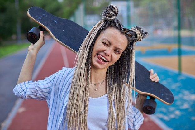 Retrato de uma garota engraçada em pé segura um longboard sobre os ombros e mostra a língua na foto de alta qualidade da câmera