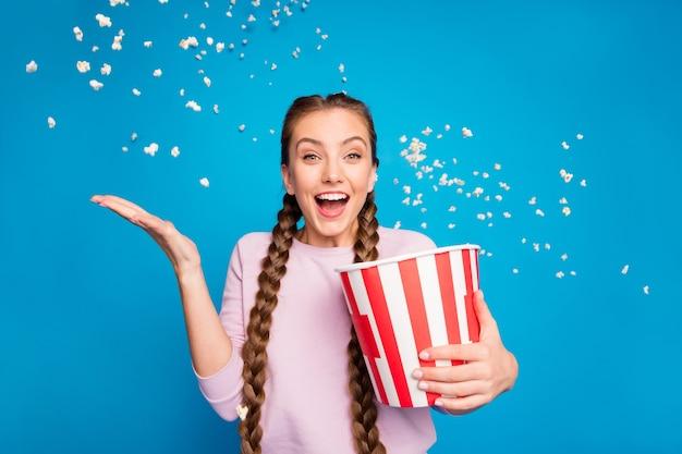 Retrato de uma garota entusiasmada e animada segura a caixa com pipoca voando, caindo no vento, enquanto assiste o grito do canal de tv da série, uau omg, use jumper rosa isolado sobre o fundo de cor de brilho