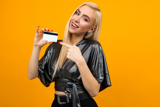 Retrato de uma garota europeia sexy segurando um cartão com uma maquete para fazer compras em um amarelo