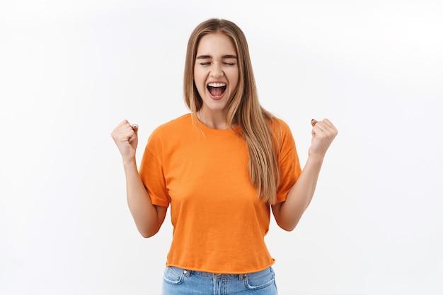 Retrato de uma garota feliz e sortuda, comemorando o sucesso, olhos fechados e sorrindo encantado