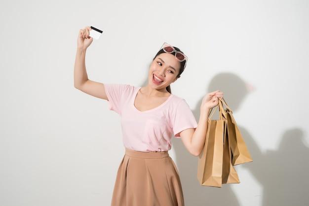 Retrato de uma garota feliz e surpresa segurando sacolas de compras e mostrando o cartão de crédito