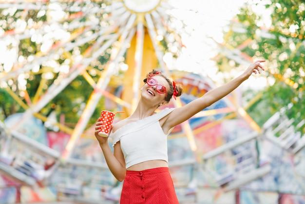 Retrato de uma garota funky positiva, segurando um copo com uma bebida ou batido em óculos engraçados vermelhos levantou a mão, desfrutando e sorrindo, sobre um fundo brilhante