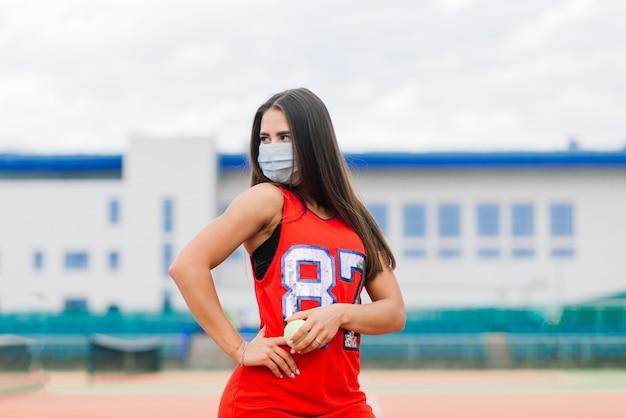 Retrato de uma garota jogadora de tênis segurando uma bola do lado de fora com máscaras protetoras
