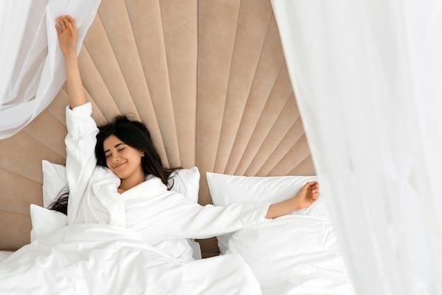 Retrato de uma garota linda e atraente, aproveitando o tempo na cama depois de dormir debaixo do cobertor, fazendo alongamento, mantendo os olhos fechados.