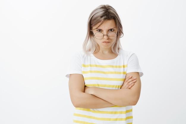 Retrato de uma garota loira indignada com óculos posando no estúdio