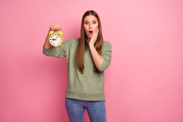 Retrato de uma garota louca atônita segurando o relógio grito impressionado