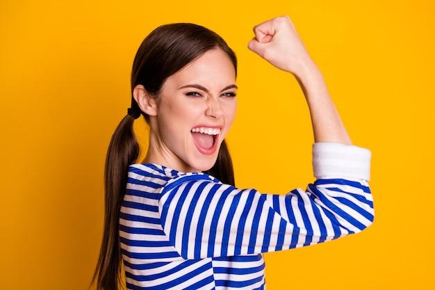 Retrato de uma garota louca e encantada, aproveite o esporte de loteria, ganhe, levante os punhos, grite, sim, use roupas bonitas isoladas sobre um fundo de cor brilhante