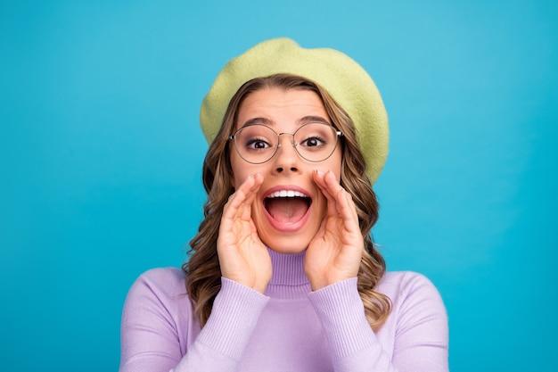 Retrato de uma garota louca e enérgica com lábios de palma gritando na parede azul
