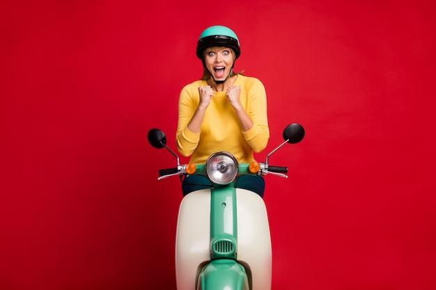 Retrato de uma garota louca e radiante sentada em uma motocicleta levantando os punhos
