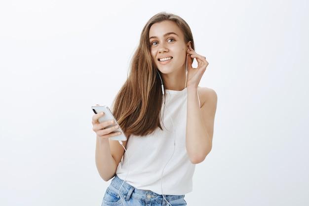 Retrato de uma garota moderna e atraente colocando fones de ouvido, ouvindo podcast ou música no celular