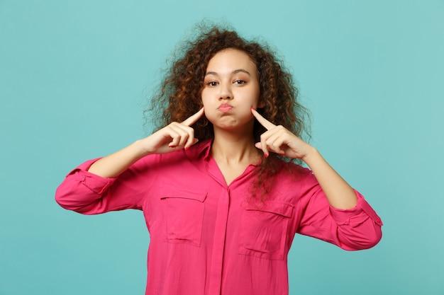Retrato de uma garota muito africana em roupas casuais, apontando o dedo indicador em soprar as bochechas isoladas no fundo da parede azul turquesa. emoções sinceras de pessoas, conceito de estilo de vida. simule o espaço da cópia.