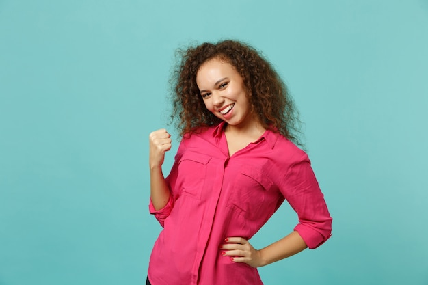 Retrato de uma garota muito africana sorridente em roupas rosa casuais, fazendo o gesto de vencedor isolado no fundo da parede azul turquesa no estúdio. conceito de estilo de vida de emoções sinceras de pessoas. simule o espaço da cópia.