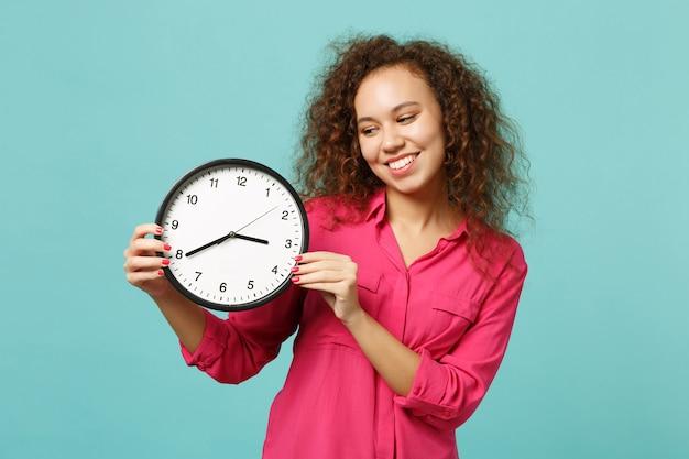 Retrato de uma garota muito africana sorridente em roupas rosa casuais, segurando o relógio redondo isolado no fundo da parede azul turquesa no estúdio. emoções sinceras de pessoas, conceito de estilo de vida. simule o espaço da cópia.