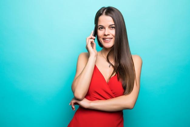 Retrato de uma garota muito alegre em um vestido vermelho falando no celular isolado sobre uma parede azul